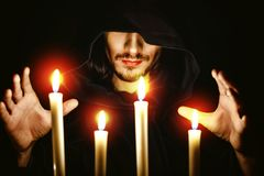 A monk with a candle. The monk in the dark over the candle idly by stock images