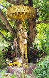 Monk carrying umbrella statue. Bronze monk carrying umbrella statue under the tree Royalty Free Stock Photo