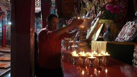 Monk changing ghee oil in the ritual oil lamp. Tibetan monk changing ghee oil in the ritual oil lamp stock video footage