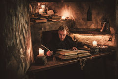 Monk chronicler writes an ancient manuscript. Bearded monk chronicler writes on the historic festival ancient scroll Stock Photo