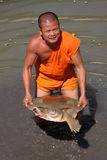 A monk of Conservation project for Cantor turtles. A monk shows a big turtle on November 25, 2012 in Kratie, Cambodia. Monks have launched a new conservation Stock Photos