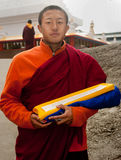 Monk at Do Drul Chorten Stupa. A Buddhist monk holding a copy of Buddhist manuscript in hand at Do Drul Chorten Stupa at Sikkim, India Royalty Free Stock Photo