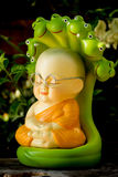 Monk doll meditating to luminosity. Located under the trees in the park at the temple stock images