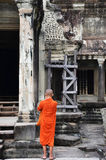 Monk enters an ancient temple at Angkor Wat Royalty Free Stock Images