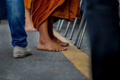 Monk foot. Foot of Thai monk during he stop walking for received some food in the morning time stock image