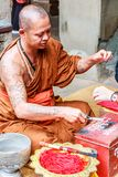 Monk giving blessings. Angkor Wat, Cambodia - 11th January 2018: Monk giving blessings and tying good luck string bracelets. This is in exchange for donations stock photography