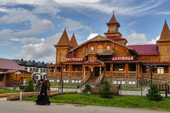 The monk goes by wooden hotel. Tobolsk Royalty Free Stock Photo