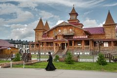 The monk goes by wooden hotel. Tobolsk Royalty Free Stock Photos