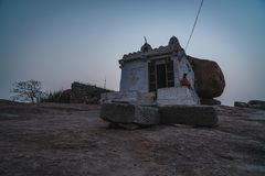 A monk hindu baba sitting on a stone temple at sunset in hampi karnakata royalty free stock photo