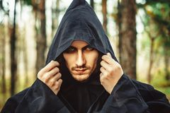 A monk in the hood. The guy in the black robe, standing in the dusk in the woods royalty free stock photos