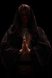 Monk with a hood on his head praying Stock Image