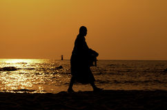 Monk on Hua Hin beach with silhouette. Thailand stock photography