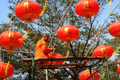 A Monk Installing Chinese lanterns Royalty Free Stock Photo