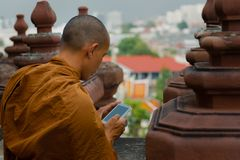 Monk looking at smart-phone royalty free stock photography