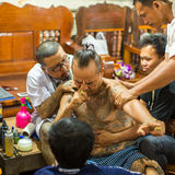 Monk makes traditional Yantra tattooing during Wai Kroo Master Day Ceremony in Bang Pra monastery royalty free stock photo