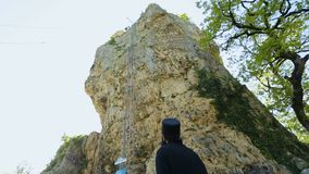 Monk observing Katskhi Pillar with ancient church on top in Chiatura, Georgia stock video