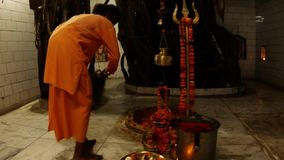 Monk in orange clothes waves with fan near shivlinga decorated with flowers evening hindu ceremony Aarti inside Shiva temple