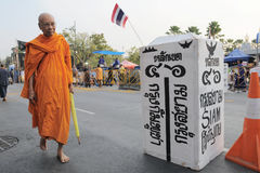 Monk passes a mock border at a Bangkok protest Royalty Free Stock Image