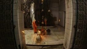 Monk performs Hindu ritual with fire near statue of bull Nandi inside Shiva temple big banyan tree bells trident flowers night