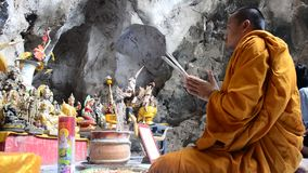 Monk praying with buddha statue in cave. Of Cave Kuhasawan temple on July 22, 2015 in Nakornsawan, Thailand stock footage
