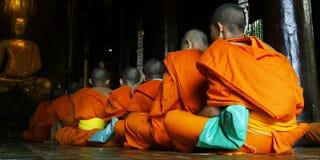 Monk praying. Detail of orange dress of monk during praying in buddhist temple Stock Photos