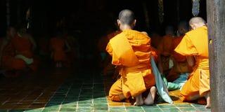 Monk praying. Detail of orange dress of monk during praying in buddhist temple Stock Image