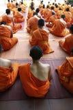 Monk praying. Detail of orange dress of monk during praying in buddhist temple Stock Photography