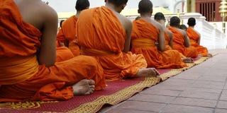 Monk praying. Detail of orange dress of monk during praying in buddhist temple Royalty Free Stock Photography