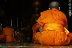 Monk praying. Detail of orange dress of monk during praying in buddhist temple Stock Photo