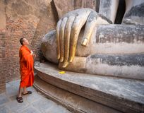 Monk praying in front of Big Buddha Statue in Wat Si Chum, Sukhothai Historical Park, Thailand stock photography