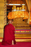 Monk praying in front of shrine with sacred Buddha figures Stock Photo