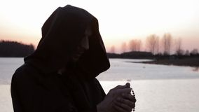 A monk prays the rosary, reads a prayer stock footage
