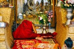 A Monk prays to a Buddha statue near Yangon. stock photos