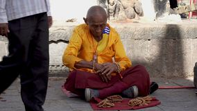 The Monk Prepares for Prayer. The Old Monk Prepares for Prayer Near the Buddhist Temple. Nepal stock footage
