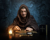 Monk - priest by candlelight - Bible reading Royalty Free Stock Image