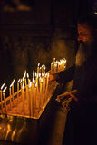 Monk puts candles in the church royalty free stock photos
