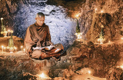 Monk reading book inside cave Stock Photography