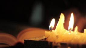 Monk reading and touching a yellow pages of old book. Close-up candle light. stock video footage