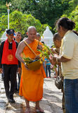 Monk receiving flower offering from people Royalty Free Stock Photo