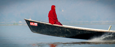 Monk in red robe sitting on a motorboat. At Inle Lake Burma Myanmar stock images