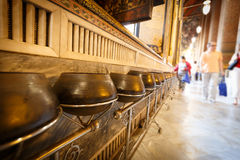 Monk's alms bowl. Close focus onto the monk's alms bowl set on the rack along with temple's wall. Blurry people on distance dropping coins into the alms royalty free stock photos