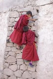 Monk's games. Two young monks climbing wall stock photos