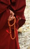 Monk's hand with bead Stock Photo