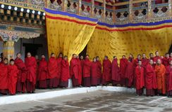 Monk's Parade. Many buddhist monks watching a rehearsal for punakha tsechu (dance festival) in one inner courtyard at punakha dzong in bhutan The Punakha Dzong royalty free stock image