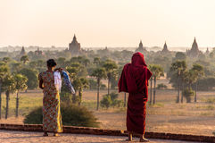 A Monk`s view over Bagan. A burmese woman with a monk looking over the pagdodas of Bagan, Pyathada Temple in Bagan, Myanmar Royalty Free Stock Photos