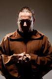 Monk in shadow. Portrait of medieval monk with cross rosary in shadow Stock Photo