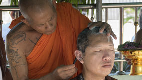 Monk shave hair of man who will become buddhism monk in ordinati Stock Photo