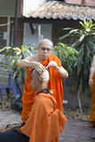 Monk shave man's hair before buddhist monk ordination ceremony Stock Image