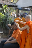 Monk shave man's hair before buddhist monk ordination ceremony Royalty Free Stock Image