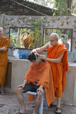 Monk shave man's hair before buddhist monk ordination ceremony Stock Images